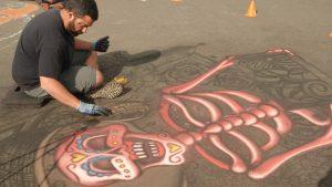 local artist chalking a sidewalk